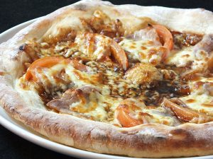 石窯ピッツアの「黒豚とトマトのピッツア」。照り焼き風のソースと黒豚とトマトが旨い。980円(税別)